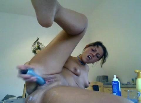 De hitsige huisvrouw smeert de seksspeeltje met boter in en mastubeerd