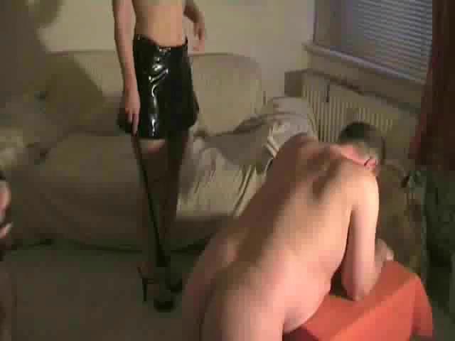 drie meesteressen die een mannelijk slaaf sexueel slaan