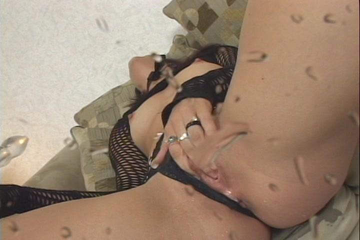 Liggend in sensueel lingerie en met latex laarzen aan ontvangst ze een spuitend orgasme